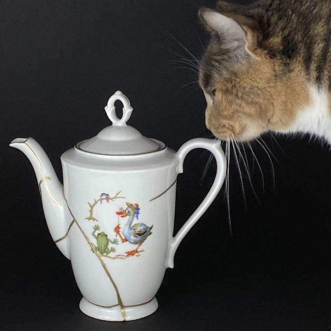 Eine weiße Kanne repariert mit der Kintsugi-Technik. Katze begutachtet die Arbeit.