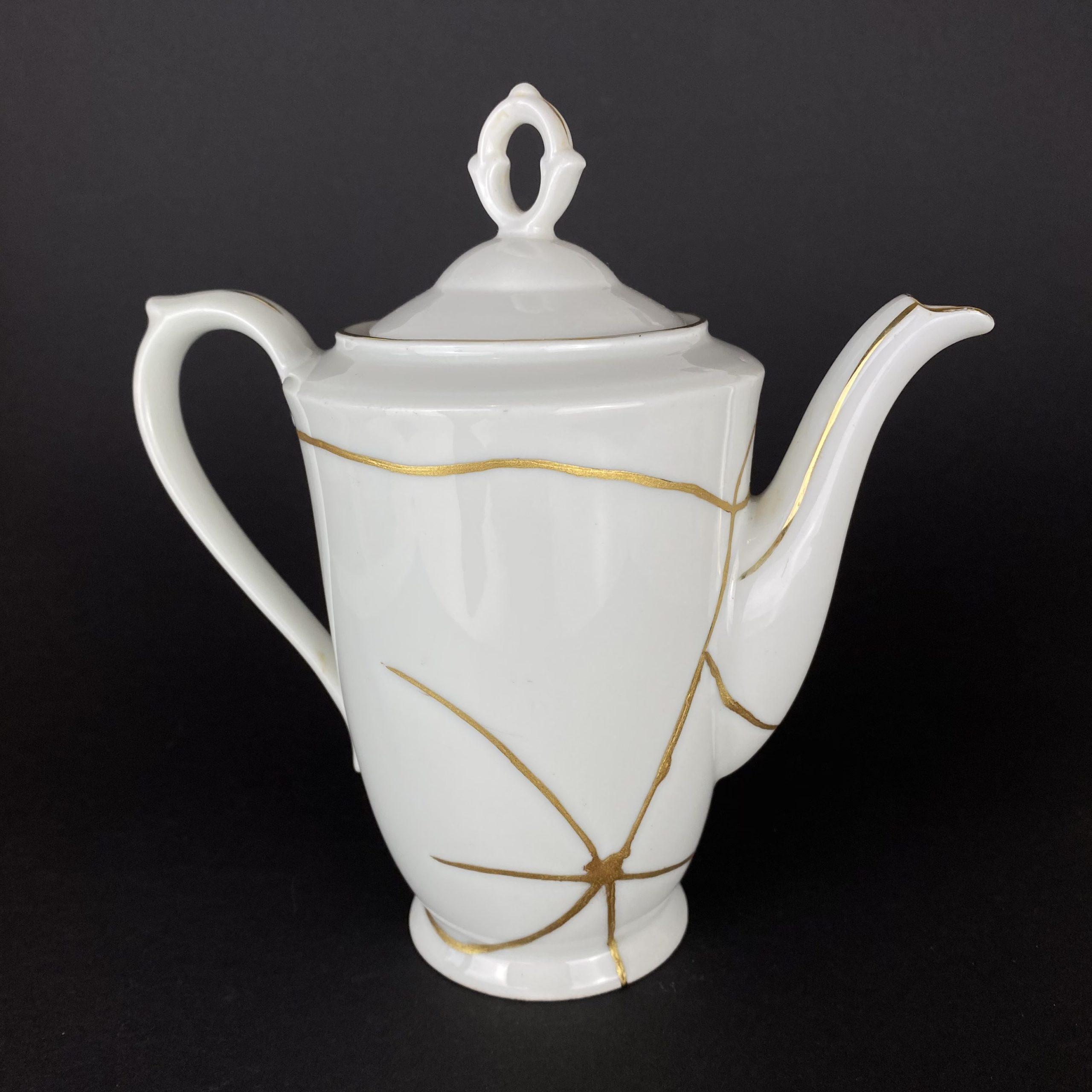 Eine weiße Kaffeekanne mit goldenen Klebenähten. Restauriert mit der Kintsugi-Technik.