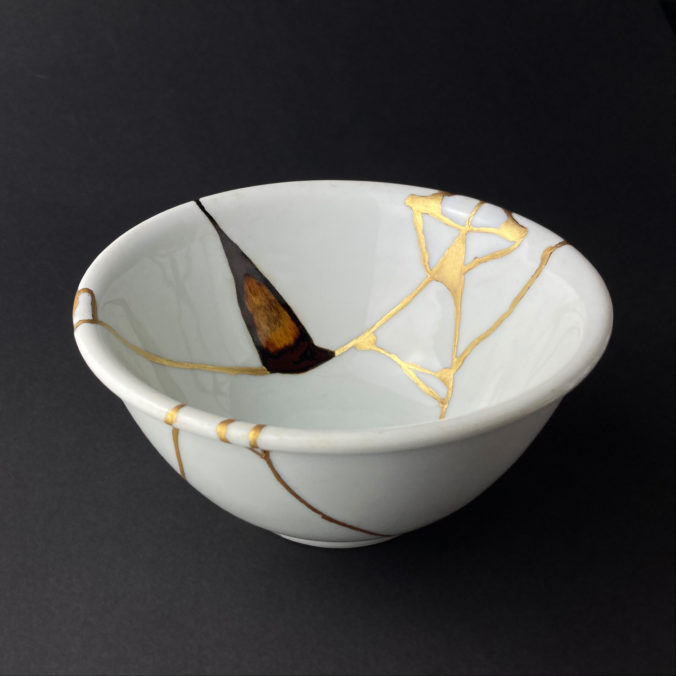 Weiße Schale restauriert mit kintsugi (Gold) und yobitsugi (Holz) eine lebensmittelechte Reparatur Technik